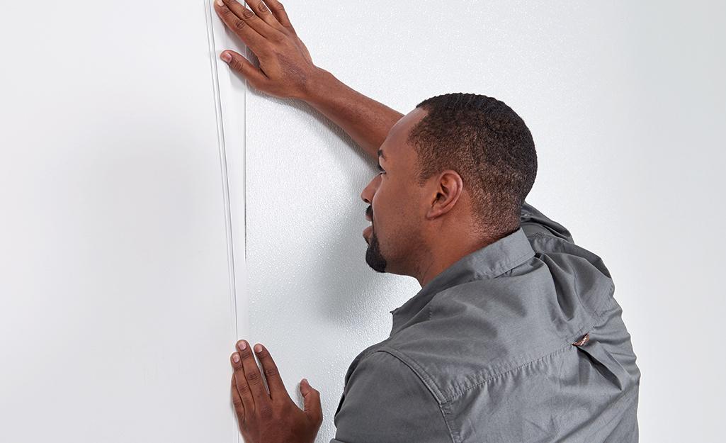 Man installing corner support rail of FRP paneling.