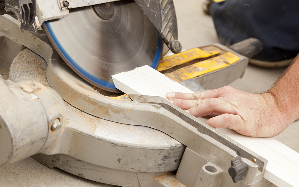 A person use a compound miter saw to cut baseboard trim.