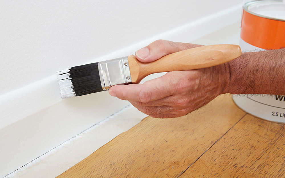 A person painting baseboard trim.
