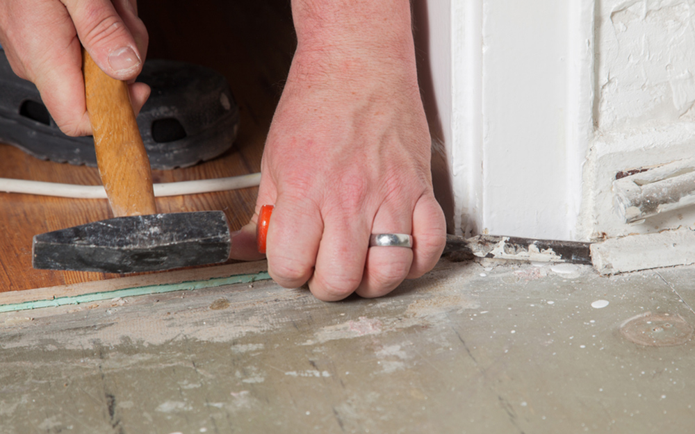 A person removing old baseboard trim.