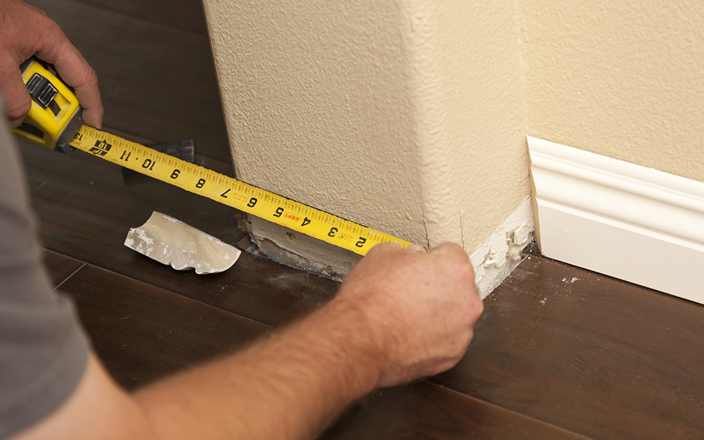 A person measuring wall for baseboard trim.