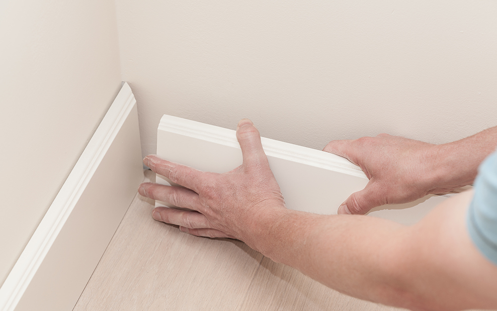 A person putting placing trim to the inside corner of a wall.