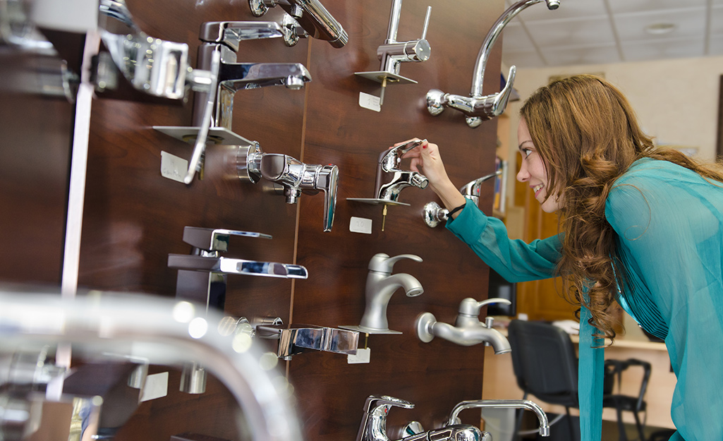 A shopper adjusting the handle of a bathroom faucet on a wall of samples in a store.