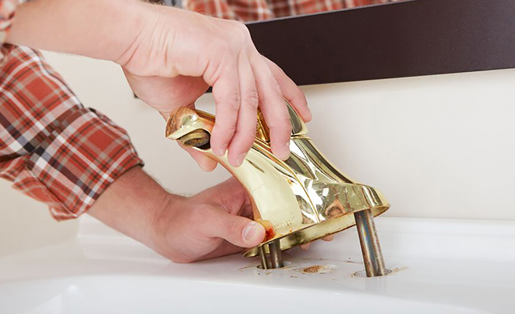 A person removing a bathroom faucet from a sink.