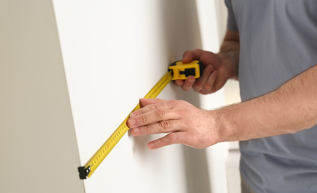 A person measures the vanity area.