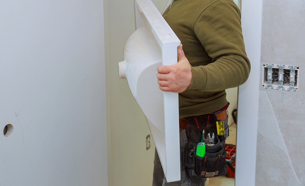 A person holding a vanity top for a new bathroom vanity.