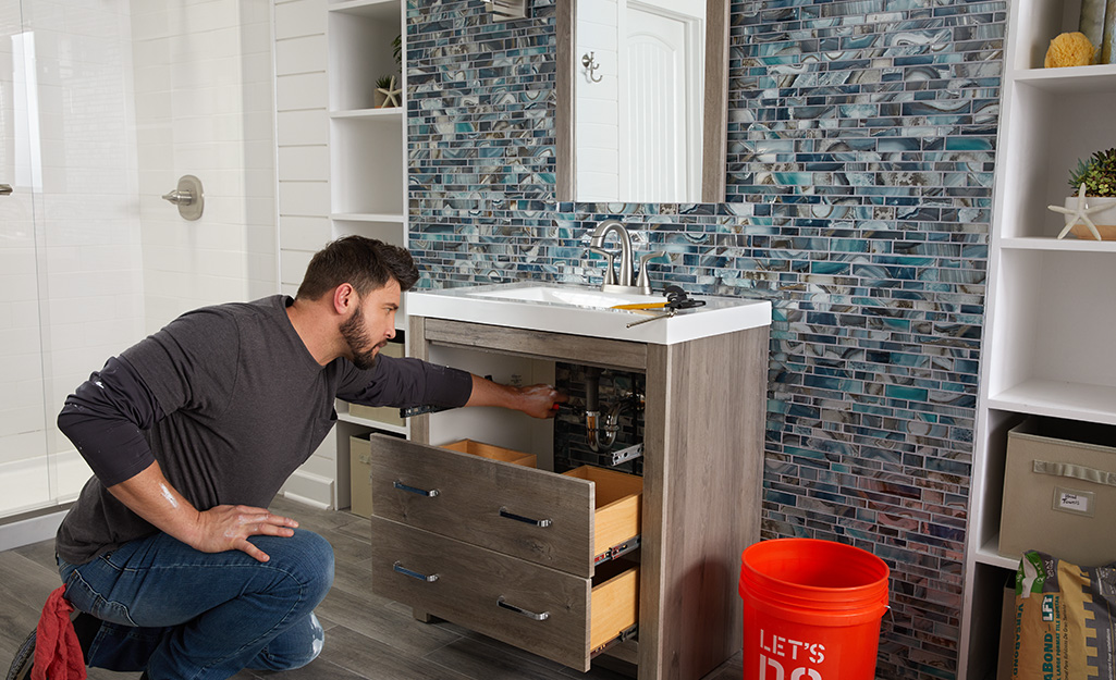 A man installing plumbing connections under a new vanity.