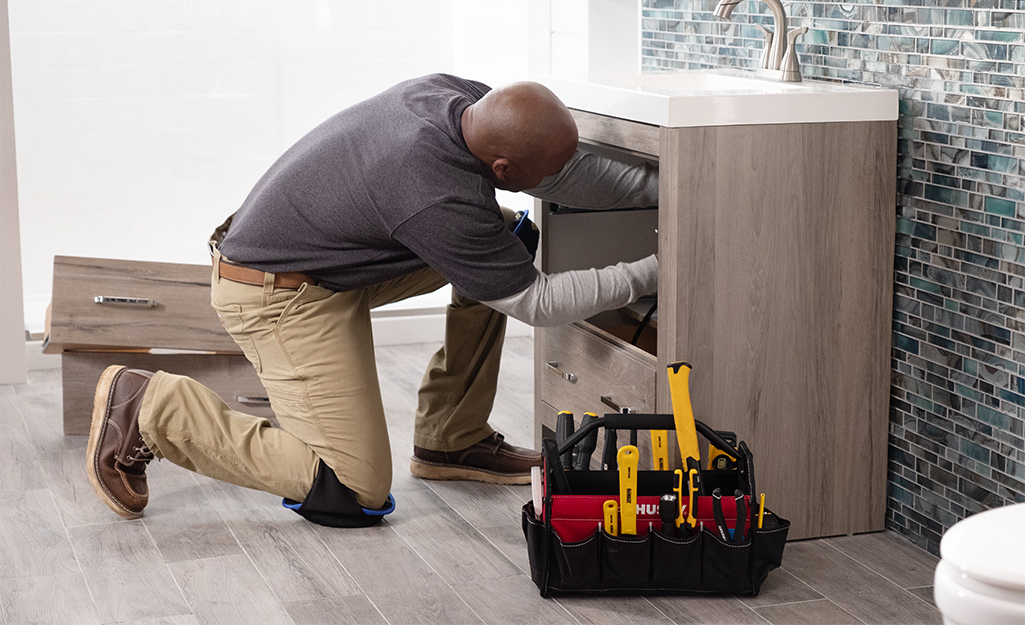 A man installing parts under the sink of a bathroom vanity.