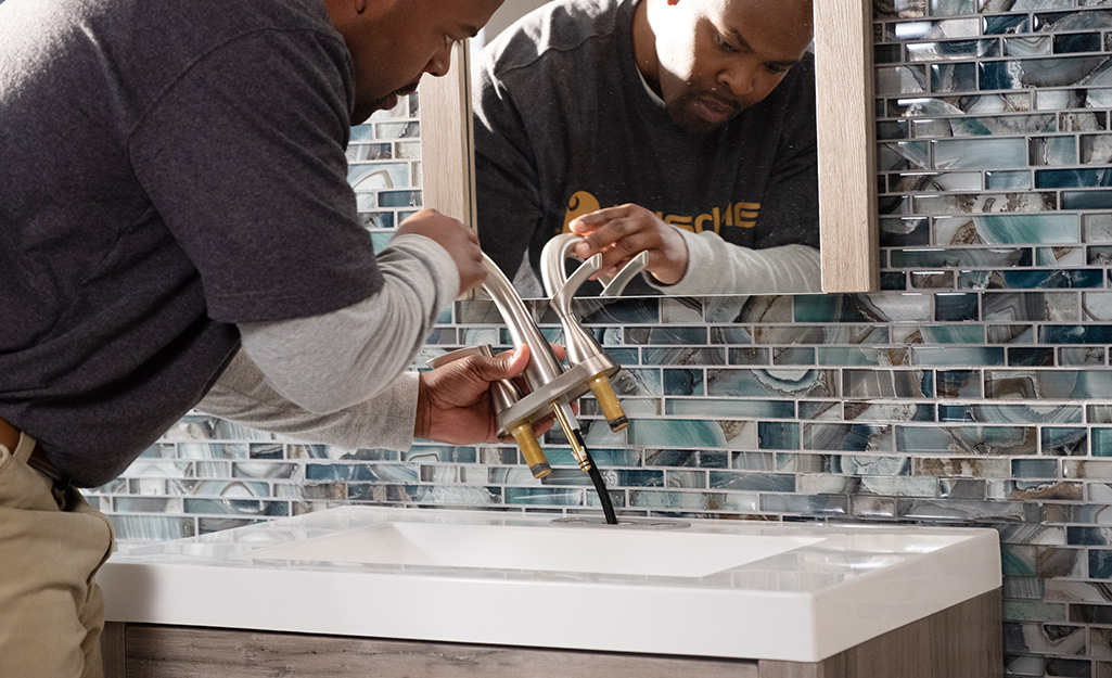 A person attaches a faucet to a vanity.