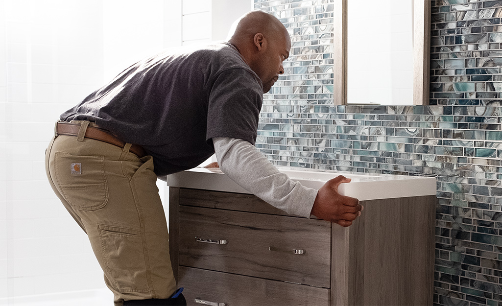 A man secures a vanity in a bathroom.