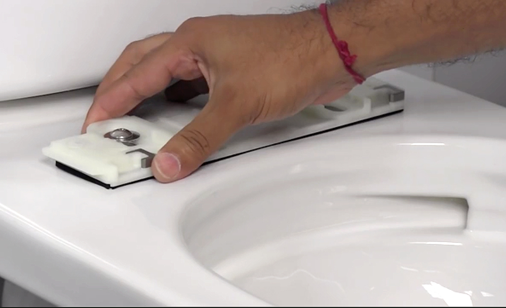 A person attaches a bidet seat mounting plate to the rim of a toilet.