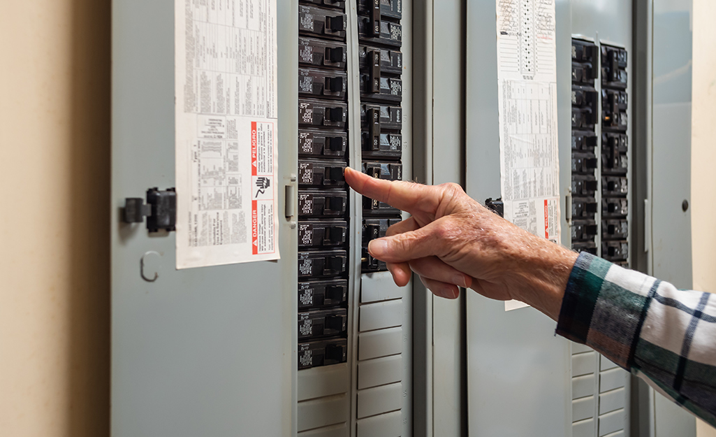 A person turning off a circuit switch in a circuit breaker.