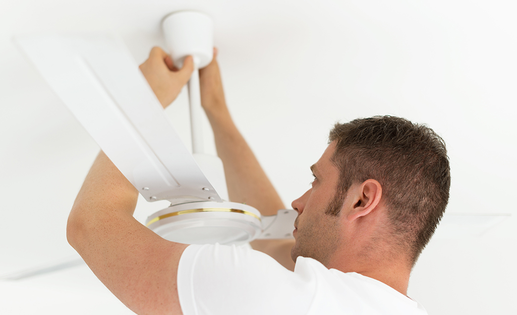 A man mounting a ceiling fan downrod.
