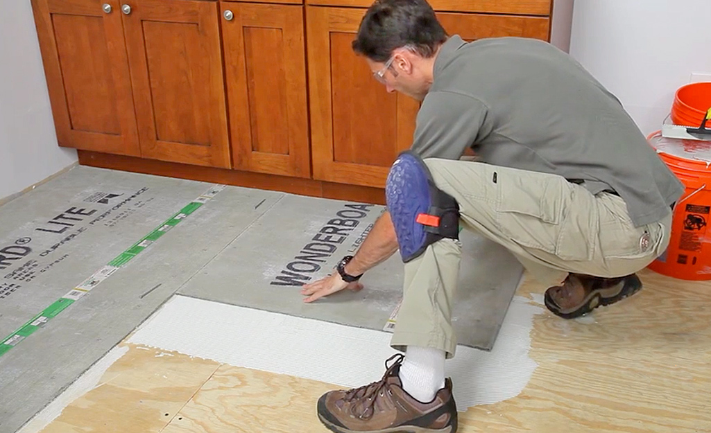 A man lays cement backerboard sheets over mortar.