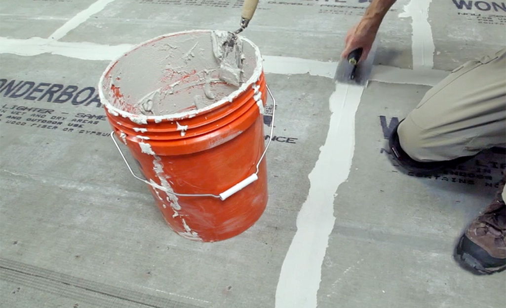 A person covers fiberglass tape with mortar.