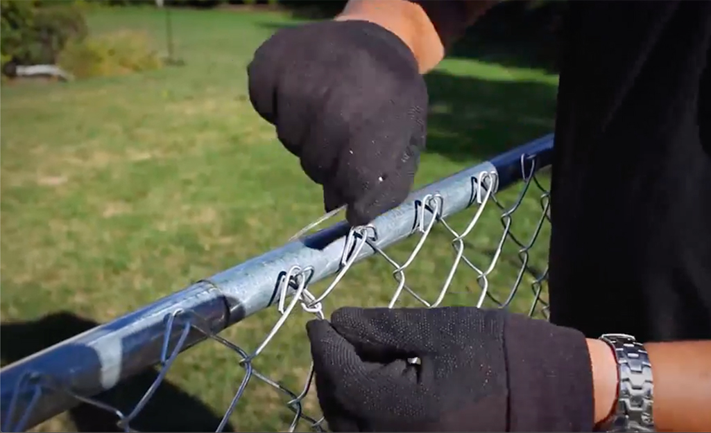 Someone attaching the metal mesh to the top bar of a chain link fence.