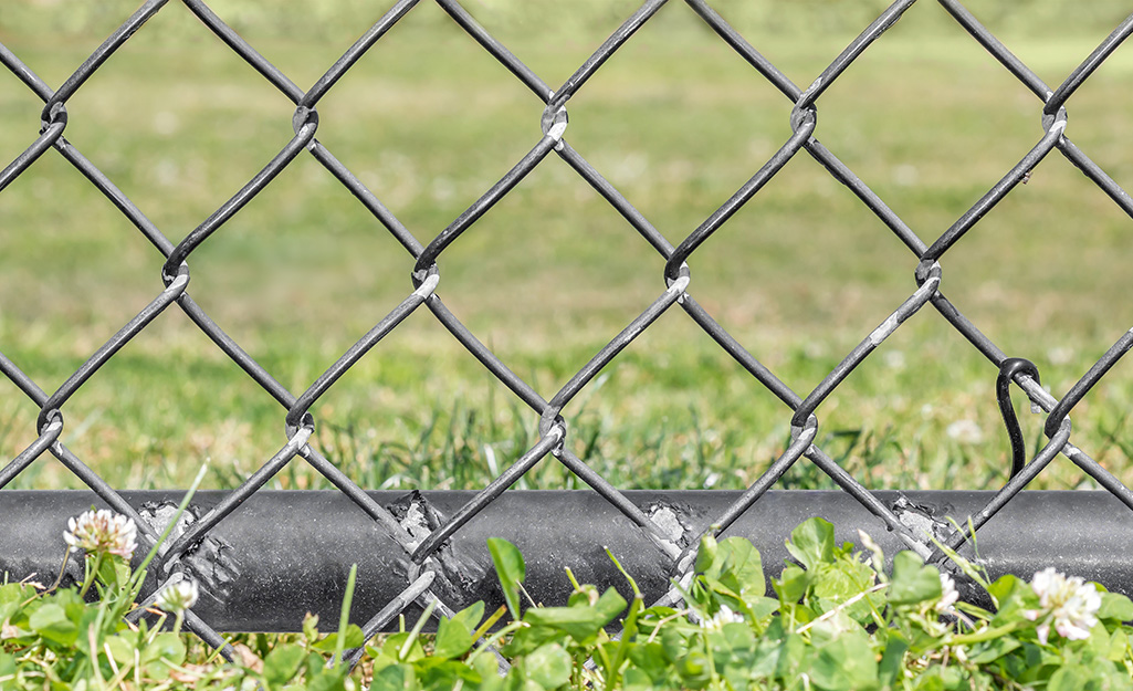 Bottom loops of a chain link fence wired to the ground bar.