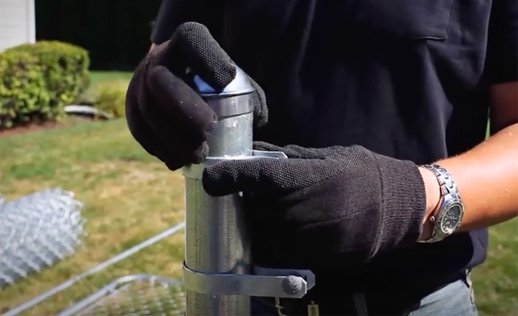 A person uses a fence puller to stretch chain link mesh