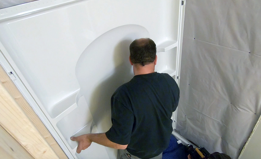 A person dry fitting the back wall of a shower enclosure.