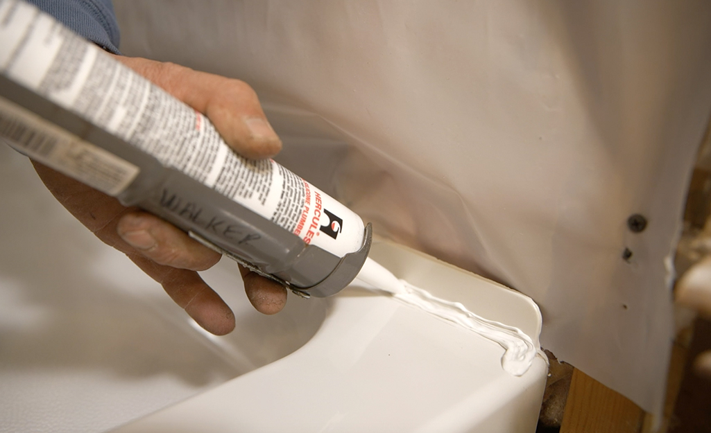 A person applying caulk to a shower panel.