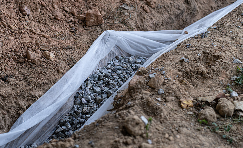A trench lined with landscape fabric and filled with gravel.