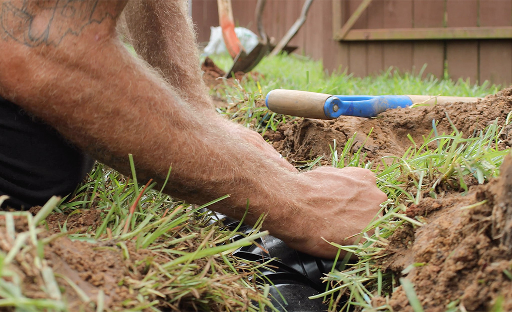 A person connecting French drain piping.