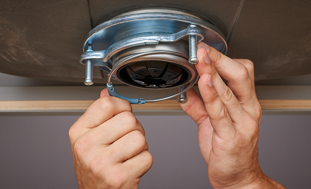 A person attaches a garbage disposal mounting ring to the flange.