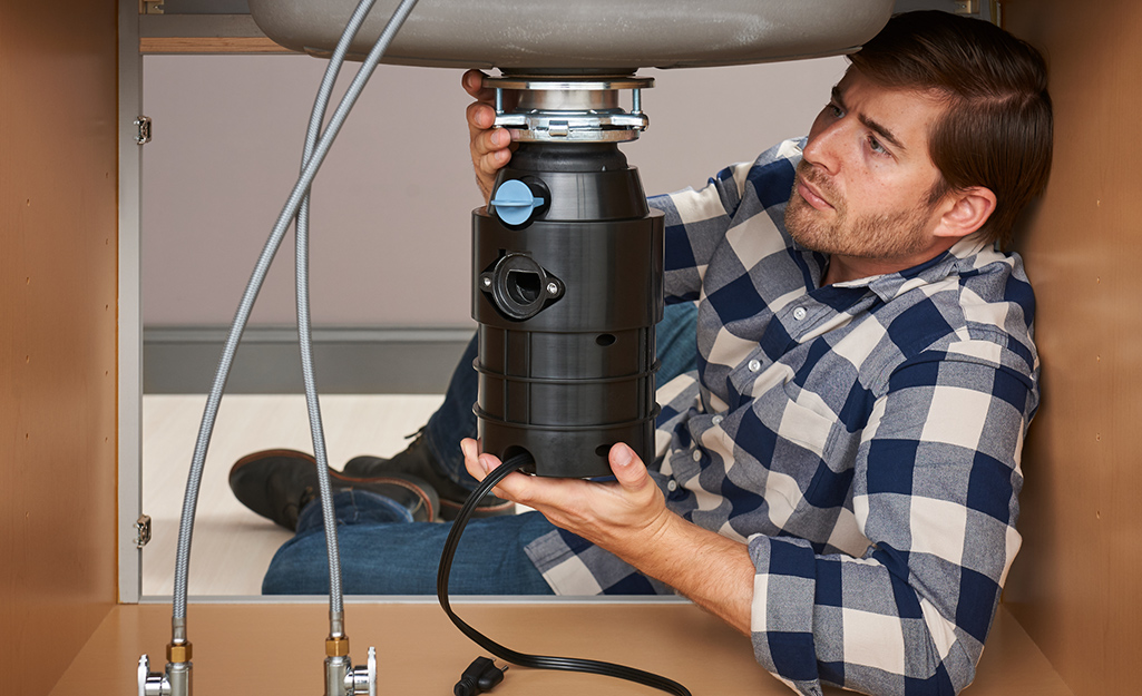A person attaches a garbage disposal to a mounting ring,