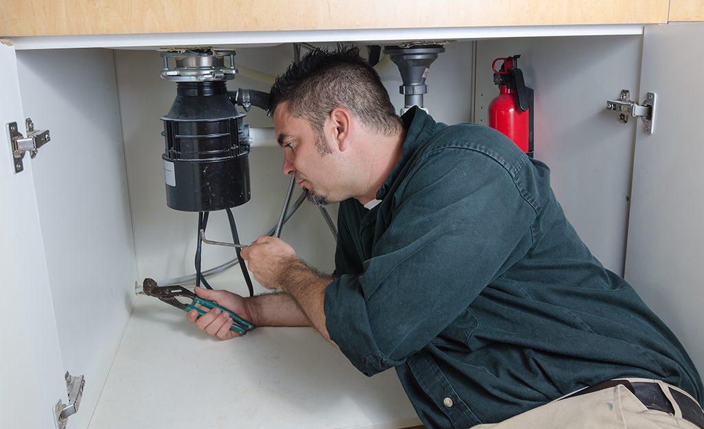 A person connects a tube to a garbage disposal.
