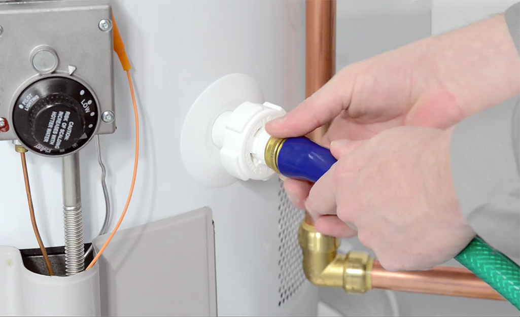 A person attaches a hose to a water heater to drain the water.