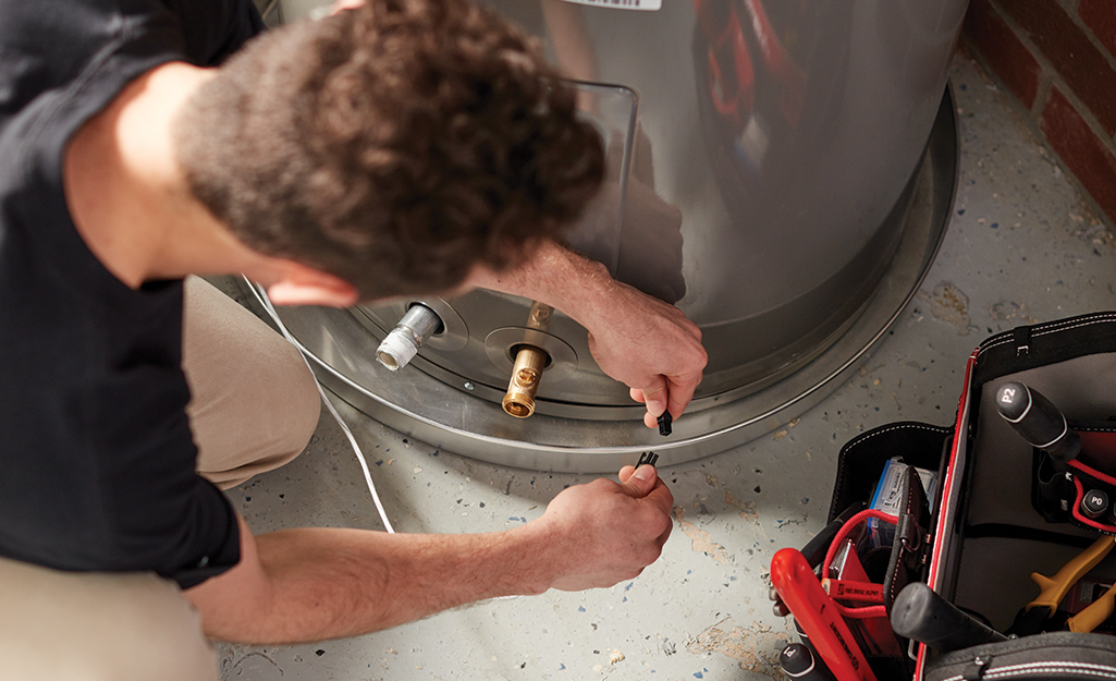 A person attaches the ventilation hood to a new water heater.