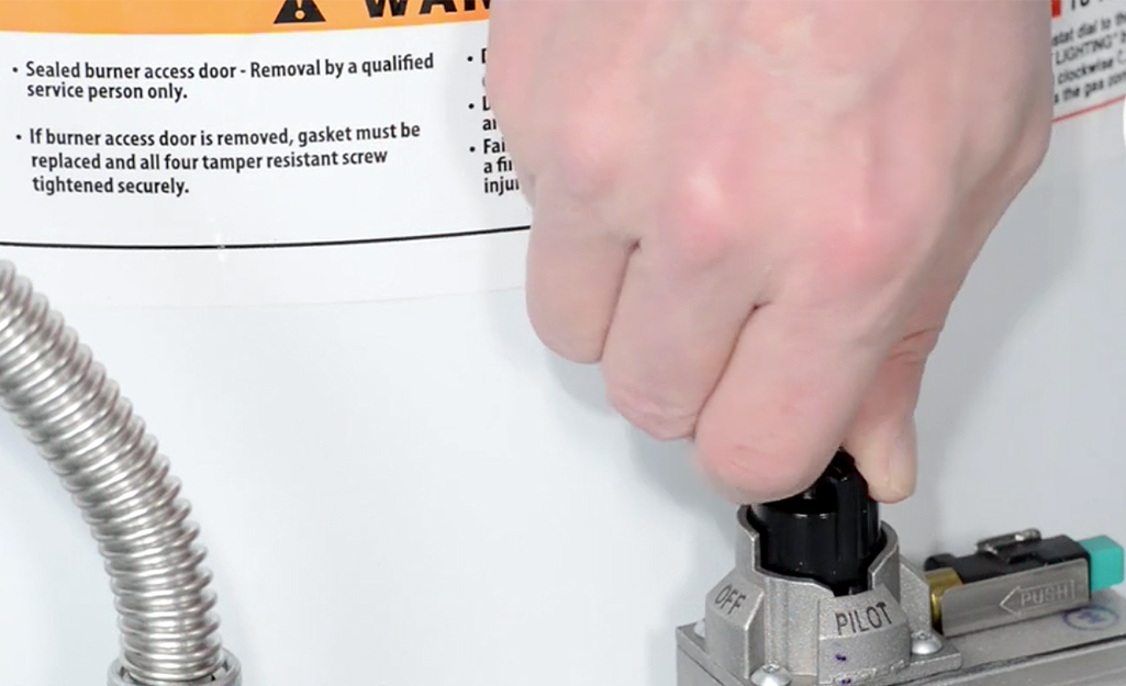 A person turns the pilot light switch on a gas water heater.