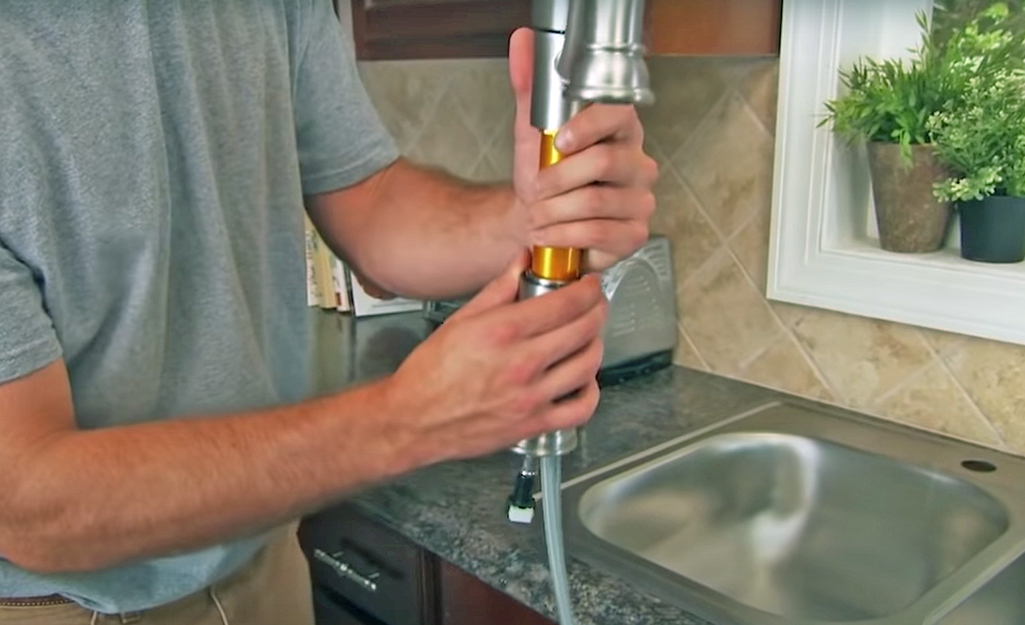 A person installs a new kitchen faucet.