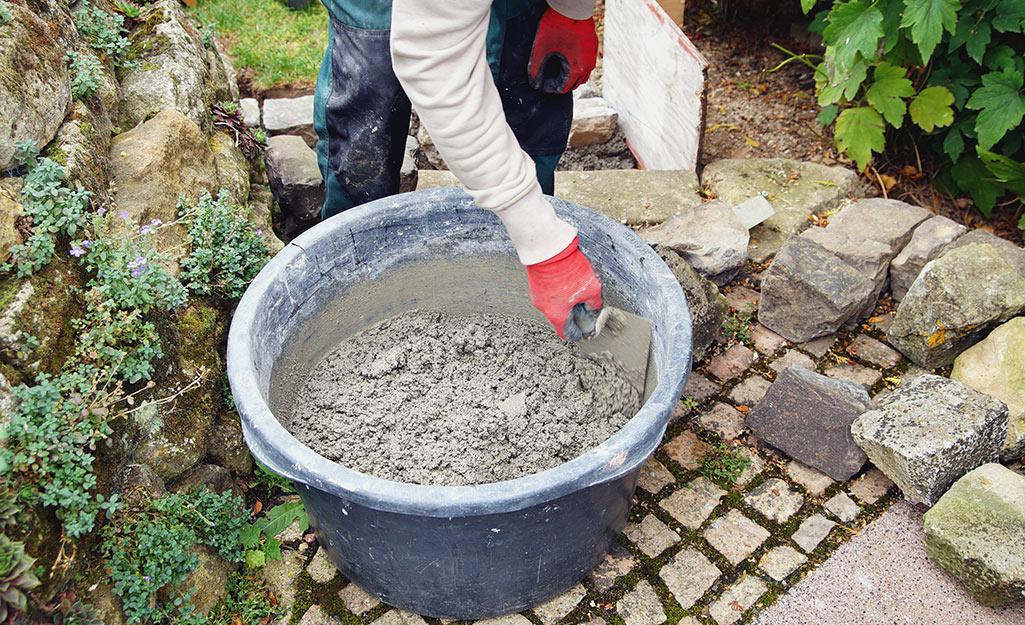 Someone making concrete in a blue plastic bucket.