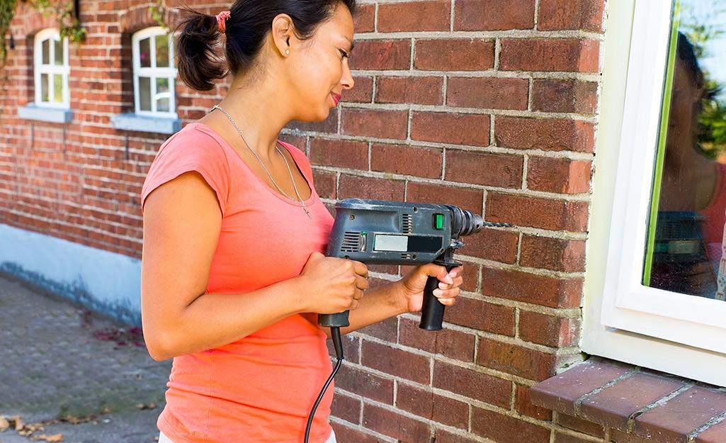 A person drilling a hole in a brick facade.