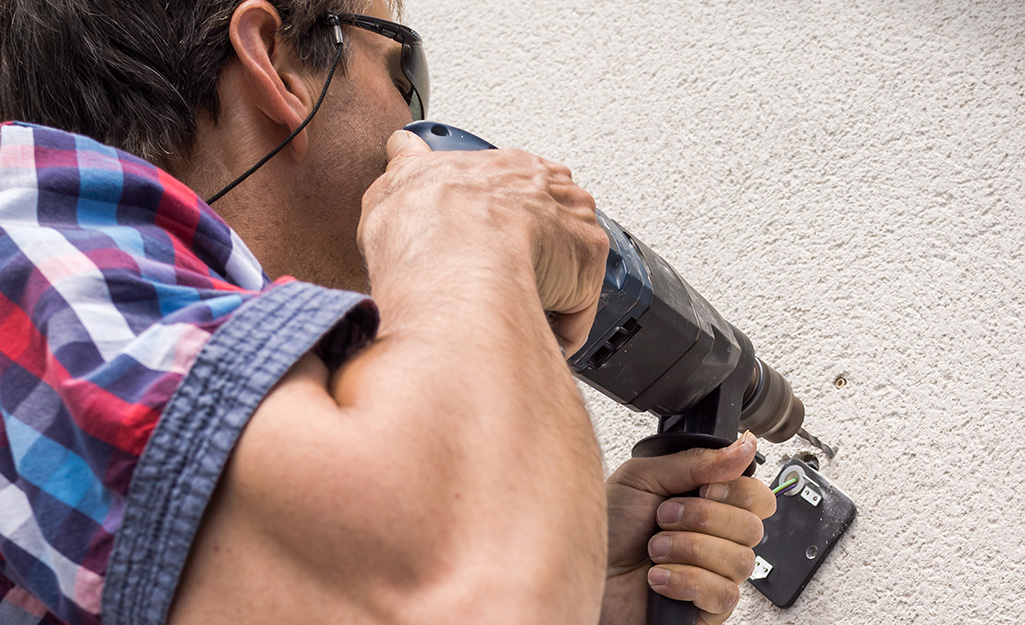 A person installing wall-mounted hardware.