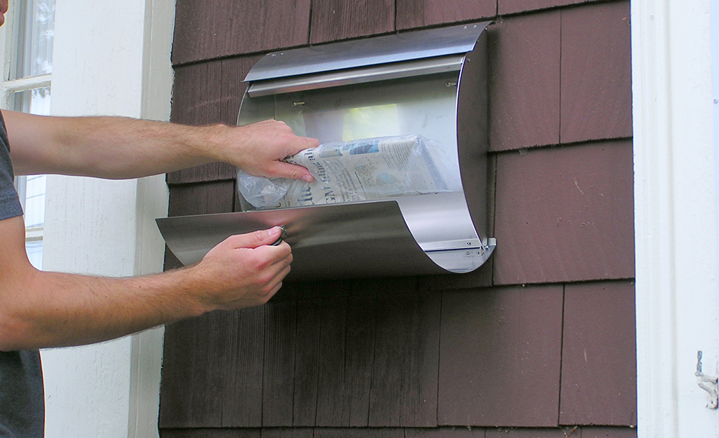 A person getting mail from a wall mounted mailbox.