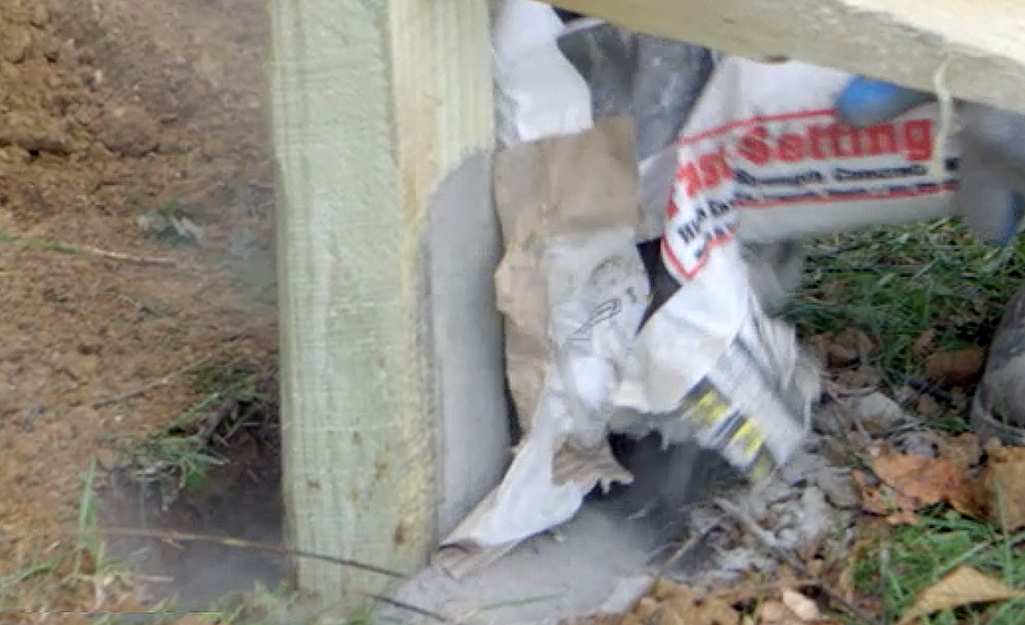 A person pouring concrete into a post hole.