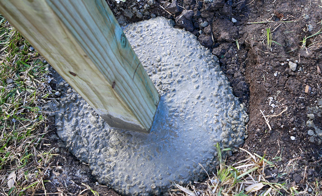 A mailbox post in hardening concrete.