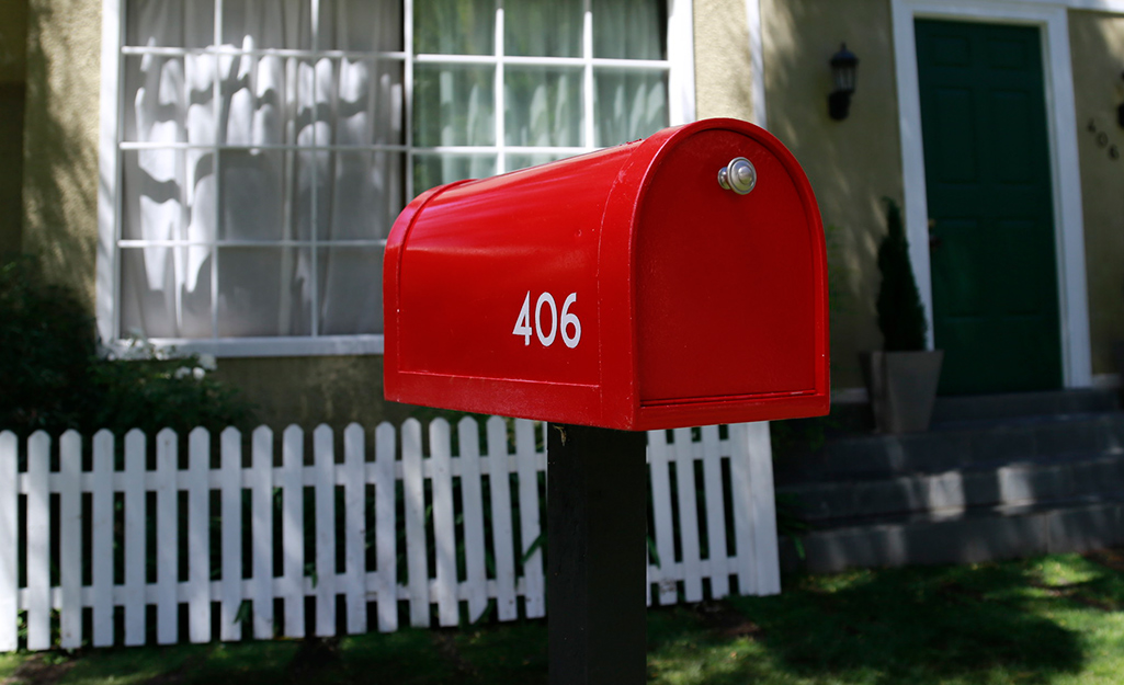 A red mailbox with white street numbers.