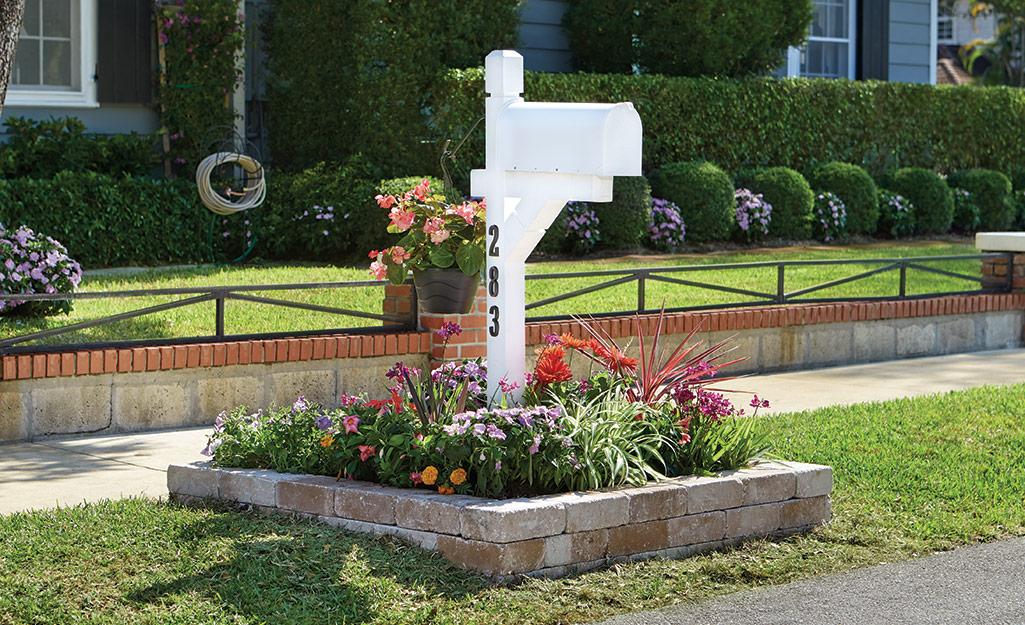 A white mailbox in a curb garden.