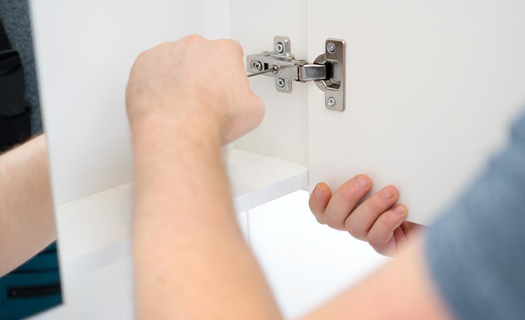 Có người dùng tuốc nơ vít vặn vào bản lề cửa tủ thuốc.