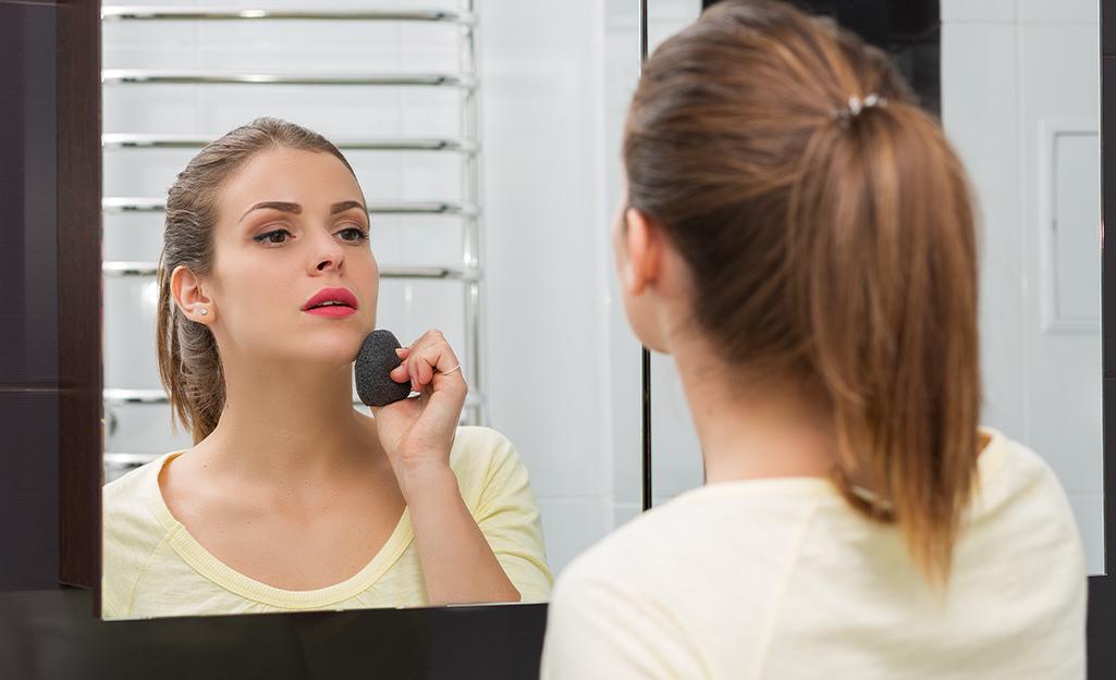 Một người phụ nữ nhìn vào gương tủ thuốc trong phòng tắm khi trang điểm.