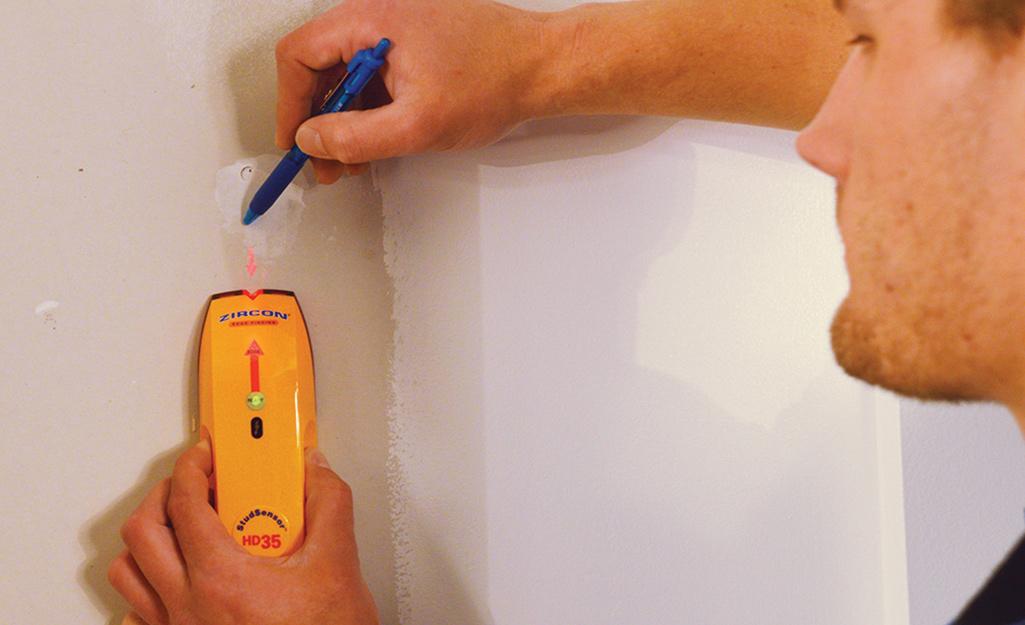 Một người đàn ông sử dụng công cụ tìm đinh tán để đánh dấu các đinh tán trên tường.