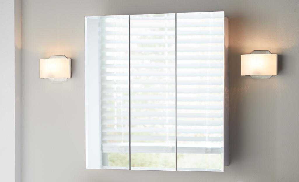 Một tủ thuốc với ba chiếc gương được lắp đặt giữa hai đèn treo tường màu xám.