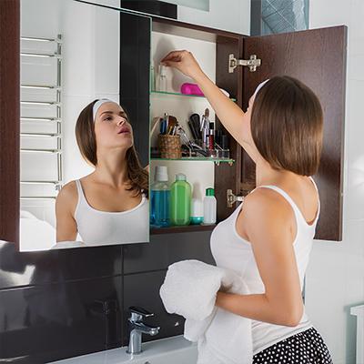 A woman putting items into a bathroom medicine cabinet.