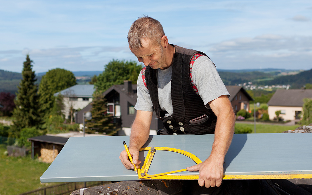 A man taking measurements of a roof.