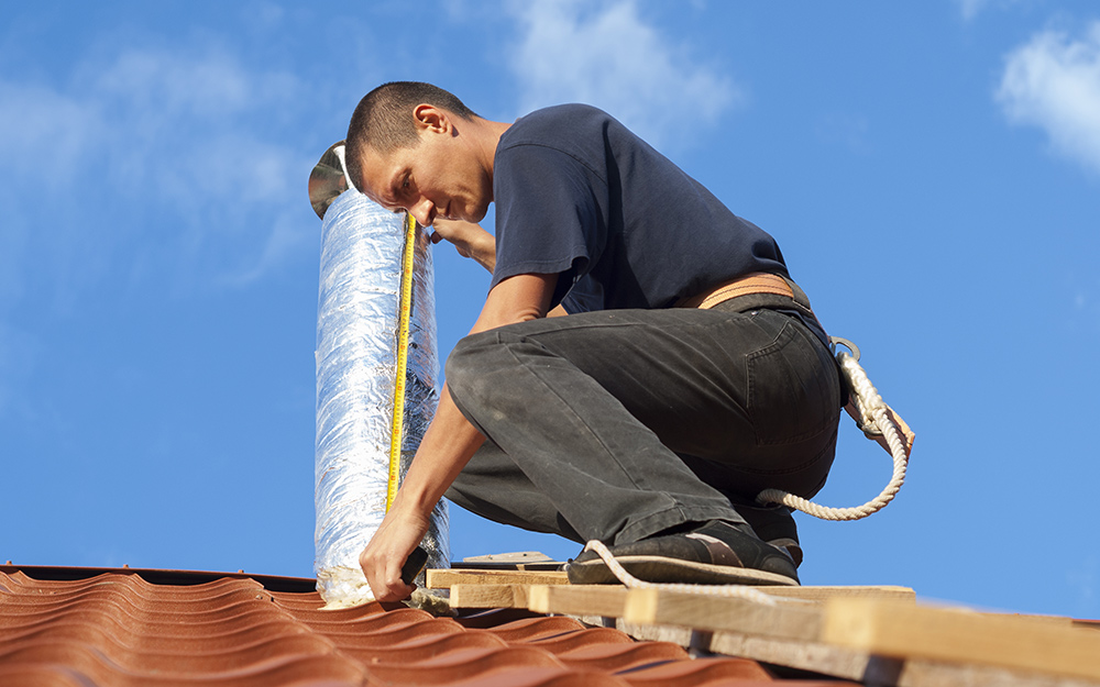 A man installing a vent on a metal roof.