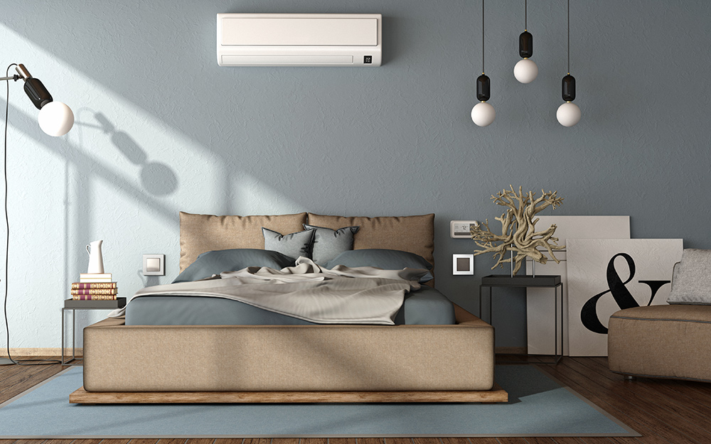 A mini split air conditioner on the wall inside a bedroom