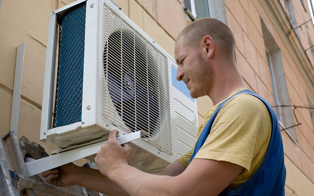 A man installing the outdoor unit of a mini split air conditioner on the exterior of a home